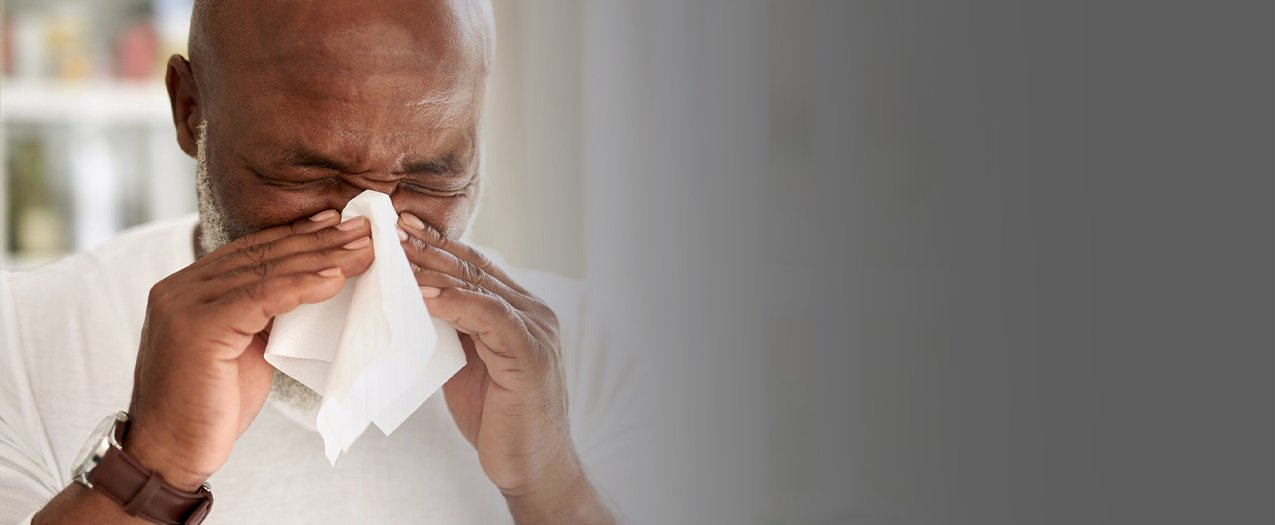 man sneezing from spring allergies